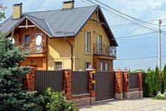 Cerca do metal de Brown com uma porta na rua com as árvores verdes decorativas na frente de uma grande casa privada fotos de stock royalty free