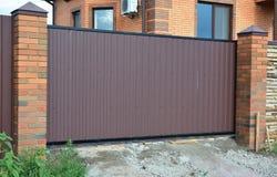 Cerca do tijolo e do metal com porta do metal do exterior rachado decorativo da superfície da parede de tijolo do projeto moderno Imagens de Stock