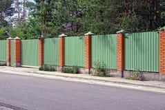 Cerca e portas verdes na frente da estrada asfaltada Foto de Stock Royalty Free