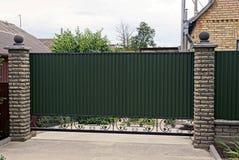 Cerca e portas verdes na frente das casas privadas Imagens de Stock