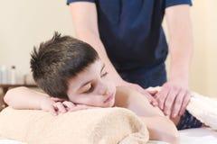 Cerca encima de un niño pequeño se relaja de un masaje terapéutico El terapeuta de sexo masculino del masaje hace un masaje médic fotografía de archivo