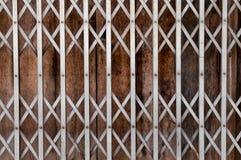 Cerca flexible del hierro del estilo retro con la pared de madera Fotos de archivo libres de regalías