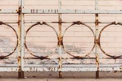 Cerca oxidada vieja en el fondo de una casa del ladrillo libre illustration