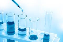 Cerca para arriba, científico que cae el líquido azul en los tubos de ensayo foto de archivo libre de regalías
