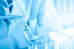 Cerca para arriba, científico que vierte el líquido azul en los tubos de ensayo, concepto de equipo de laboratorio en experimento foto de archivo libre de regalías