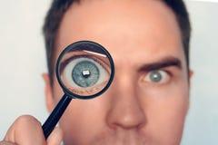 Cerca para arriba de la cara del hombre con la lupa cerca de un ojo en el fondo blanco Visión para redondear el ojo humano con fotografía de archivo libre de regalías