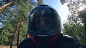 Cerca para arriba de la cara del motorista en un casco mientras que se mueve metrajes