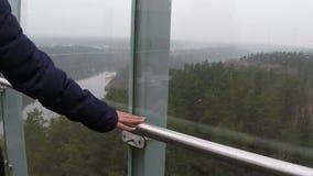 Cerca - para arriba de la diapositiva de la mano de una mujer en la verja en una altura de vistas concepto del recorrido metrajes