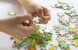 Cerca para arriba de las manos del niño que juegan con rompecabezas coloridos en la tabla ligera Temprano aprendiendo foto de archivo