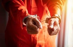 Cerca para arriba de las manos del preso con las esposas en mono anaranjado en la prisión fotografía de archivo