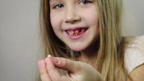 Cerca - para arriba de una muchacha sonriente linda, niño que muestra un colmillo rasgado de la leche en su mano y gomas que sang almacen de video