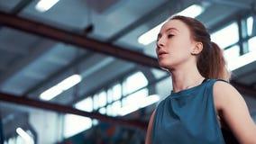 Cerca - para arriba del ejercicio atlético joven de la muchacha con pesas de gimnasia almacen de video