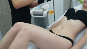 Cerca para arriba, el cosmetólogo aplica el gel especial en el estómago de la mujer antes de procedimiento de elevación metrajes