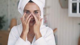Cerca para arriba, la muchacha en albornoz, con la toalla en la cabeza aplica la crema en su cara, cámara lenta almacen de metraje de vídeo