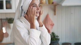 Cerca para arriba, la muchacha en albornoz, con la toalla en la cabeza aplica la crema en su cara, c?mara lenta metrajes