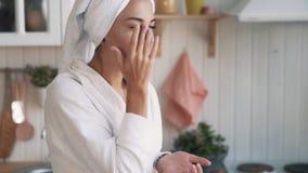 Cerca para arriba, la muchacha en albornoz, con la toalla en la cabeza aplica la crema en su cara, c?mara lenta almacen de metraje de vídeo