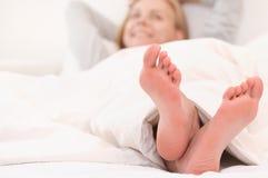 Cerca para arriba tire de los pies de la mujer que se relajan en la cama blanca por la mañana imagen de archivo libre de regalías