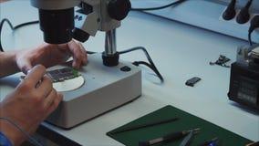Cerca para arriba, trabajador en laboratorio de prueba El especialista está probando una nueva placa madre móvil para el quadcopt almacen de video