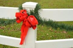 Cerca roja del blanco del adorno del pino del verde del arco de la cinta del día de fiesta Fotografía de archivo libre de regalías