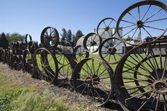 A cerca velha da exploração agrícola feita das rodas oxidadas velhas do vagão & do trator nos artesões no celeiro de Dahmen está  Imagens de Stock