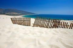 Cerca velha que fura fora das dunas abandonadas da praia arenosa Fotografia de Stock Royalty Free