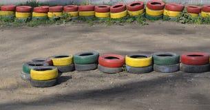 Cercado de los neumáticos pintados con la pintura de diversos colores fotografía de archivo