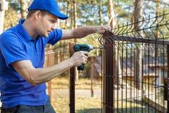 Cercado del territorio de la propiedad - el hombre atornilla el panel de la cerca del metal fotografía de archivo libre de regalías
