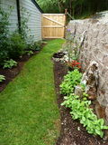 Cercado no jardim com a parede e porta de pedra do bloco no fim do verão Imagem de Stock