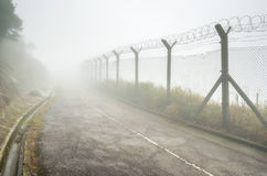 Cercado y alambre de púas de la alambrada en niebla Fotos de archivo libres de regalías