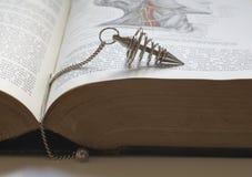 Cercando con la bacchetta da rabdomante con un vecchio libro medico fotografia stock