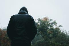 Cercando da dietro ad una figura incappucciata misteriosa bagnata da pioggia su un percorso del paese immagini stock libere da diritti