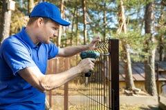 Cercando los servicios - trabajador que instala la cerca soldada con autógena de la malla metálica fotos de archivo