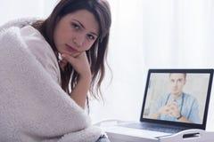 Cercando per il consiglio medico su Internet Immagine Stock