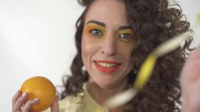 _cercano ascendente retrato joven juguetón sonreír muchacha con brillante componer sostener anaranjado y jugar con cinta Cámara l almacen de metraje de vídeo