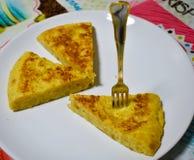 cercano para arriba de tres porciones de una tortilla española en una placa blanca en el mantel de una tabla Una porción de torti imagen de archivo