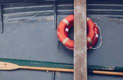 cercano para arriba de un pequeño barco viejo con la naranja de la boya - anillo de vida - humor marino imagen de archivo libre de regalías