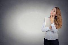 Cercare di pensiero del bello della donna computer portatile felice della tenuta Immagine Stock