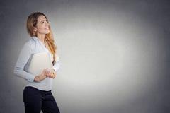 Cercare di pensiero del bello della donna computer portatile felice della tenuta Immagini Stock