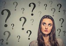 Cercare di pensiero della donna ha molte domande Immagine Stock