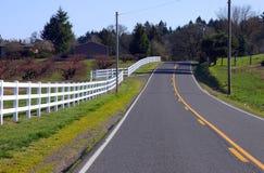 Cercas & estrada brancas. Fotografia de Stock