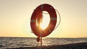 Cerchi arancio di sicurezza su una spiaggia del mare nei raggi del tramonto r stock footage