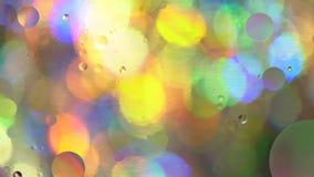 Cerchi dell'olio in acqua su un fondo colorato video d archivio