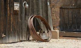 Cerchio arrugginito del metallo che pende contro una parete stagionata della plancia fotografia stock libera da diritti