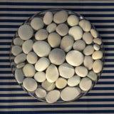 Cerchio composto di pietre bianche e grige, fondo della mandala dei ciottoli su fondo a strisce bianco blu nella luce del giorno, fotografia stock libera da diritti