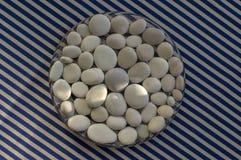 Cerchio composto di pietre bianche e grige, fondo della mandala dei ciottoli su fondo a strisce bianco blu nella luce del giorno, immagine stock libera da diritti