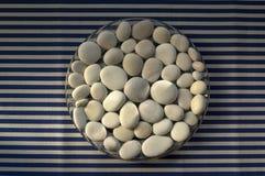 Cerchio composto di pietre bianche e grige, fondo della mandala dei ciottoli su fondo a strisce bianco blu nella luce del giorno, fotografie stock libere da diritti