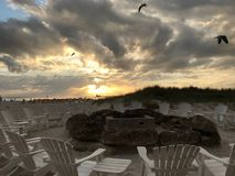 Cerchio del fuoco della spiaggia con le nuvole ed i gabbiani Fotografie Stock Libere da Diritti