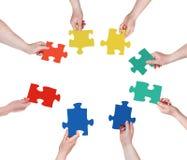 Cerchio delle mani della gente con i pezzi di puzzle Fotografia Stock