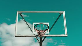 Cerchio di pallacanestro contro il lasso di tempo blu del cielo nuvoloso