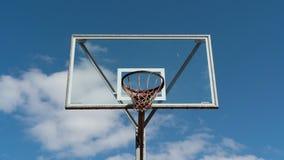 Cerchio di pallacanestro sul lasso di tempo del fondo del cielo